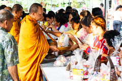 Give alms to a Buddhist monk at New year in Thailand Stock Photos