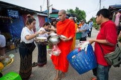 Give alms to a Buddhist monk. stock image
