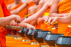 Give alms to a Buddhist monk in Thailand Stock Photo