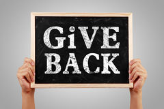 Give Back. Hands holding blackboard with text Give Back against gray background Royalty Free Stock Image