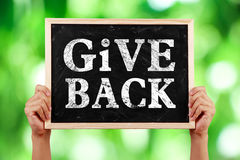 Give Back. Hands holding blackboard with text Give Back against green blurred background Stock Image