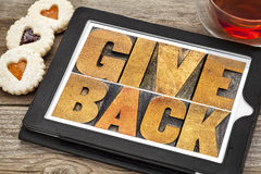 Give back typography in wood type on tablet Stock Image