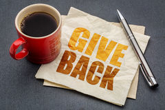 Give back word abstract on napkin. With cup of coffee against gray slate stone background Stock Photography