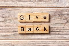 Give Back word written on wood block. Give Back text on table, concept stock photo