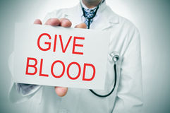Give blood. A doctor showing a signboard with the sentence give blood written in it stock image