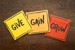 Give, gain and grow concept in sticky notes. Give, gain and grow word abstract - personal development concept, handwriting on sticky notes against rustic wood Stock Photo