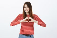 Give her sympathy to caring person. Attractive friendly-looking female freelancer with broad smile, showing heart. Gesture over chest and grinning, loving job stock photography