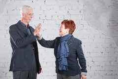 Give a high five. Happy smiling old couple standing cuddling together isolated on white brick background. copy space. Royalty Free Stock Photos