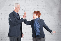 Give a high five. Happy smiling old couple standing cuddling together isolated on white brick background. copy space. Stock Images