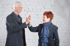 Give a high five. Happy smiling old couple standing cuddling together isolated on white brick background. copy space. Stock Image