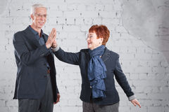 Give a high five. Happy smiling old couple standing cuddling together isolated on white brick background. copy space. Royalty Free Stock Image