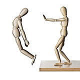 Give him a shove. Two manikins, one pushing the other off an edge Royalty Free Stock Photo
