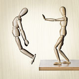 Give him a shove. Two manikins, one pushing the other off an edge Royalty Free Stock Image