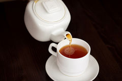 We give hot some tea. Tea time - white teacup and teapot on black background Royalty Free Stock Photo