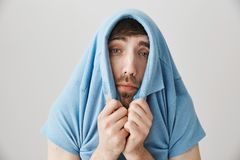 Give me break I am ill. Studio shot of miserable exhausted european guy hiding in shirt while looking through collar. With sad and tired expression, feeling royalty free stock image
