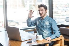 Give me five. ! Portrait of satisfied happy young businessman in blue jeans shirt are sitting in cafe and greeting a worker through a webcam and showing palm of royalty free stock images