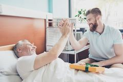 Give me five! Young stylish red bearded guy is visiting and cheering up his grandpa lying in bed at hospital ward. Give me five! Young stylish red bearded guy is royalty free stock photo