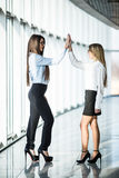 Give me high-five. Two business women give high five in modern office room Royalty Free Stock Image