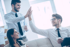 Give me high-five!. Two handsome men giving high-five and holding coffee cups with smile while sitting on the couch at office with their beautiful coworker royalty free stock images