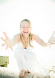 Give Me A Hug!. A naturally beautiful happy young woman with arms reaching out wearing a white dress on a bright sunny day Royalty Free Stock Images