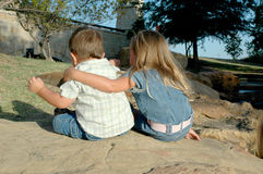 Give me hugs. Brother and sister sit on a rock with their backs to the camera. Little boy and girl with their backs to the camera. Little boy dives away from Stock Image