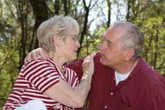 Give me a kiss. Lovely elderly couple sitting outdoors having fun Stock Photos