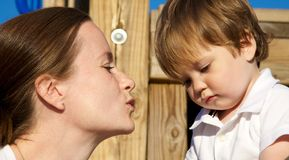 Give me a kiss. A young mother kissing her toddler Royalty Free Stock Photo