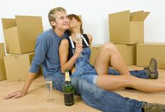 Give me a kiss!. Young couple sitting on the floor in flat. They're looking happy. Celebrating removal with champagne. Woman is kissing man Royalty Free Stock Photo