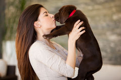 Give me a kiss!. Cute young brunette getting some puppy love from her cute Labrador Royalty Free Stock Photo