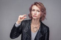 Give me a little bit. Portrait of hopeful beautiful girl with short hair and makeup in casual style black leather jacket standing. And asking for something stock photos