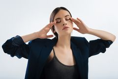 Hopeful calm woman trying to concentrate. Give me minute. Serious tired young woman massaging her eyes  while posing on the light background  and  wearing blue Stock Images