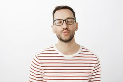 Give me mwah. Pleased sensual attractive boyfriend in black stylish glasses, folding lips and closing eyes with sligh royalty free stock image
