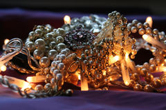 Give me pearls for christmas, honey. Pile of pearl jewelry lit with christmas lightin, on violet silk royalty free stock photography