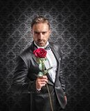 Give a rose on the anniversary. Gentleman gives a red rose on the anniversary Royalty Free Stock Images