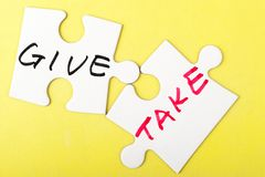Give and take. Words written on two pieces of puzzle Royalty Free Stock Photos