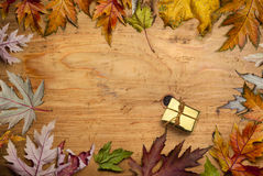Give thanks. Dried autumn leaves and gold-wrapped gift arranged on wooden table. Copy space available for additional text Stock Photo