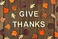 Give Thanks wooden letters and autumn leaves over rustic wood stock image