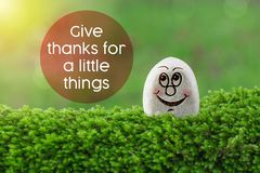 Give thanks for a little things. The text give thanks for a little things with stone smile happy face on green moss and sunshine light background royalty free stock photos