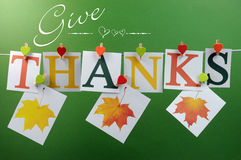 Give Thanks message hanging from pegs on a line for Thanksgiving greeting with leaves. Give Thanks message spelling in letters hanging from pegs on a line for royalty free stock photo
