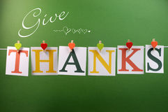 Give Thanks message hanging from pegs on a line for Thanksgiving greeting