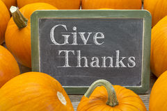 Give thanks phrase on blackboard with pumpkin. Give thanks - Thanksgiving concept - words in white chalk on a blackboard surrounded by pumpkins royalty free stock images