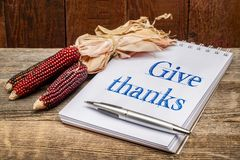 Give thanks handwriting in sketchbook. Give thanks phrase - handwriting in an art sketchbook with a decorative corn against rustic barn wood royalty free stock images