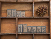 Give Thanks with pine cone - concept. The words Give Thanks in wooden letters along with a pine cone royalty free stock photo