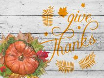 Give thanks with pumpkin and autumn leaves for thanksgiving day. On white table royalty free stock photo