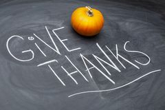 Give thanks reminder on blackboard with squash and gourds. Give thanks reminder - Thanksgiving concept - handwriting in white chalk on a blackboard with a stock photo