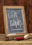 Give thanks - rustic blackboard sign. Give thanks - Thanksgiving concept - rustic blackboard sign with a decorative corn against barn wood stock photos