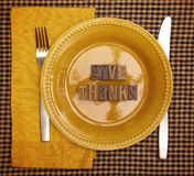 The Phrase Give Thanks Spelled in Type Set on a Plate Setting for Thanksgiving Dinner. Give Thanks Spelled in Type Set on a Plate Setting for Thanksgiving Dinner stock image