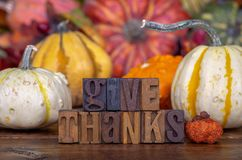 Give Thanks Text on a Colorful Background ao Autumn Squash. Give Thanks text written with wooden block letters on a colorful background of squash and gourds royalty free stock photo