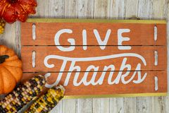Give Thanks text phrase Thanksgiving holiday background. With colorful pumpkins. Orange, white and red colors. Indian corn and wood background stock image