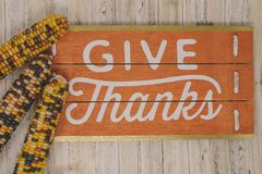 Give Thanks text phrase Thanksgiving holiday with Indian Corn. On wood background. Artistic instagram style filter applied royalty free stock photo